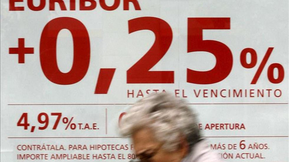 Una mujer pasa frente a un anuncio de hipotecas. EFE