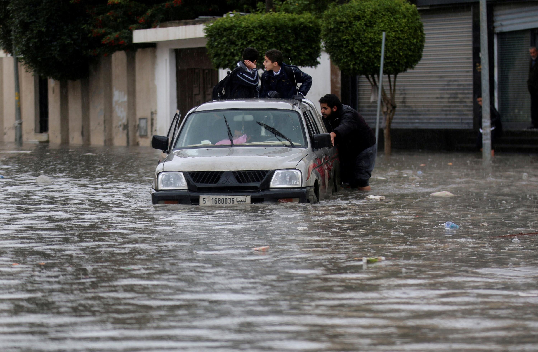 La gente empuja un vehículo a través de una calle inundada después de la lluvia en Trípoli/REUTERS