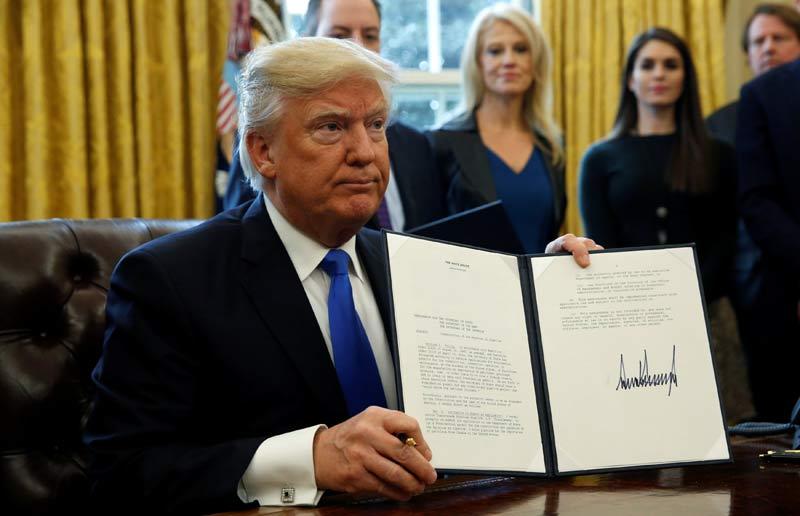 Trump enseña en el despacho oval la orden ejecutiva que da luz verde a los dos polémicos oleoductos. | KEVIN LAMARQUE (REUTERS)