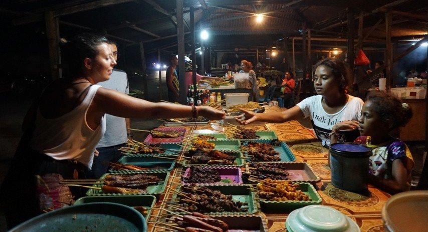 Niñas vendiendo en los puestos de pescado en el mercado nocturno de Dili.