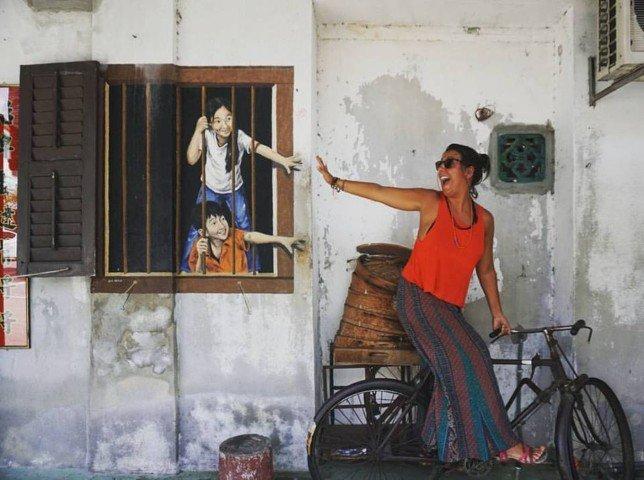 Foto mía frente a una de las muchas obras de Street Art que te encuentras por las calles de George Town (Penang, Malasia)